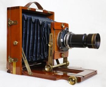Deskový přístroj formátu 13x18 cm z mahagonu firmy J. Lancaster & Son Birmingham z roku 1897 má již prakticky všechny vymoženosti profesionálních systémových velkoformátových kamer: výškový i sklopný pohyb výměnných objektivů a kipování se zadní stěnou s možností vkládaní kazet bez sejmutí matnice. Na snímku je osazen unikátním tele-zoomem Telinear 540-1080 mm což je důkazem, že konstrukce zoomů byla známá už v 19. století.  O rok později firma vyrábí už 200 000 fotoaparát (zanikla v roce 1955).. Orok později firma vyrábí už 200 000 fotoaparát (zanikla v roce 1955)..